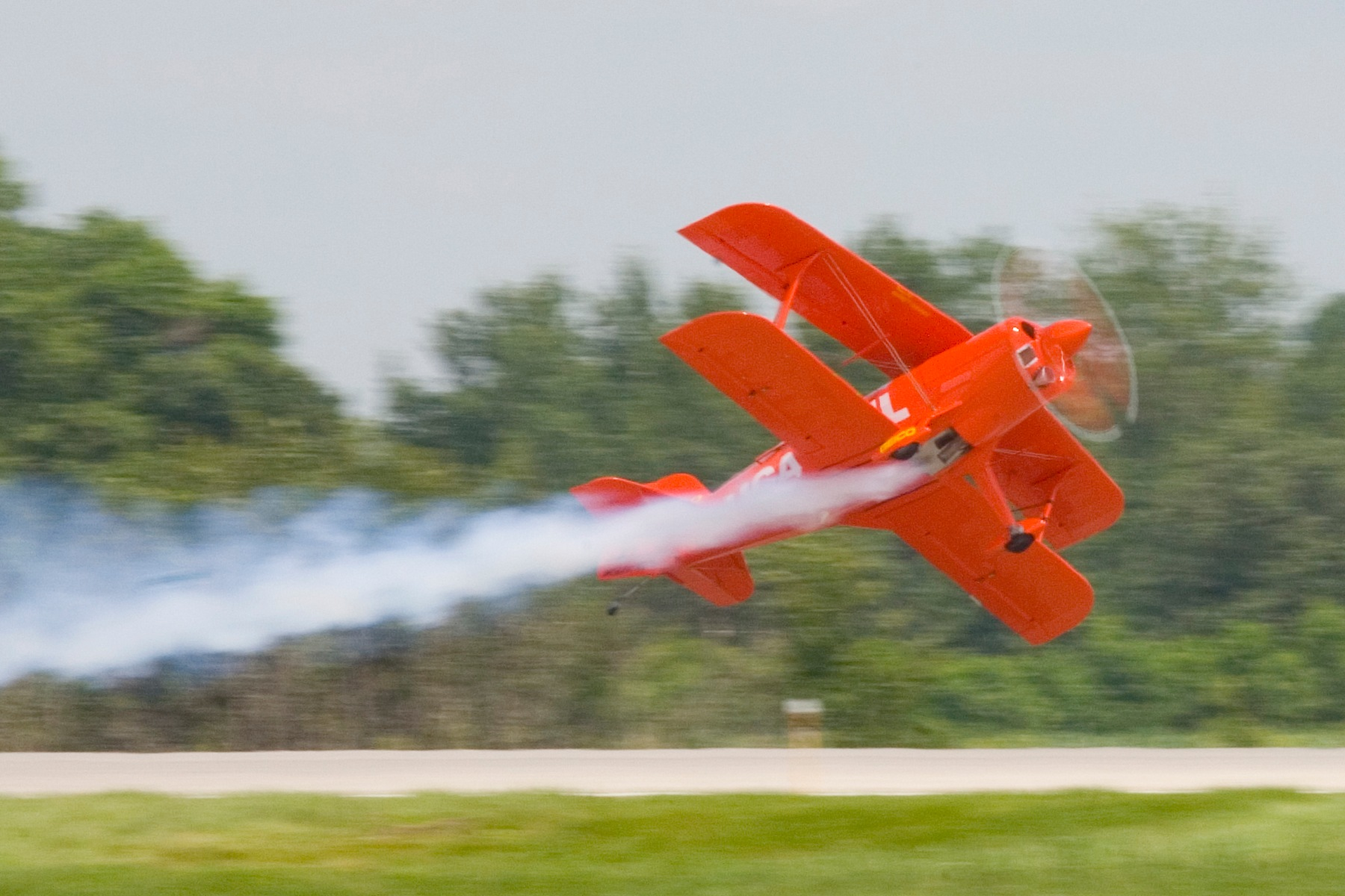 Lucas oil biplane flying sideways above runway by Bernard Mordorski