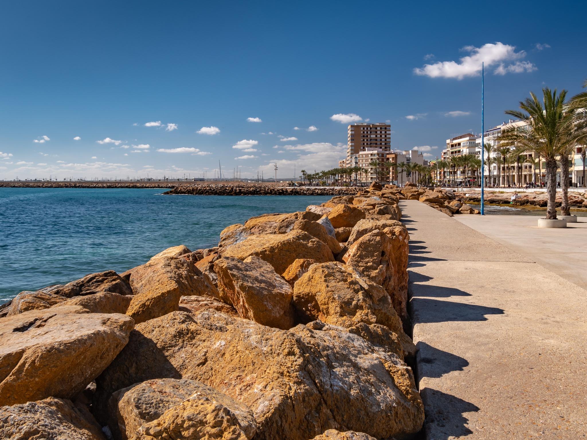 Photo in Sea and Sand #torrevieja #sea front #sea #sand #rocks #promenade #blue sky #sunny #holiday