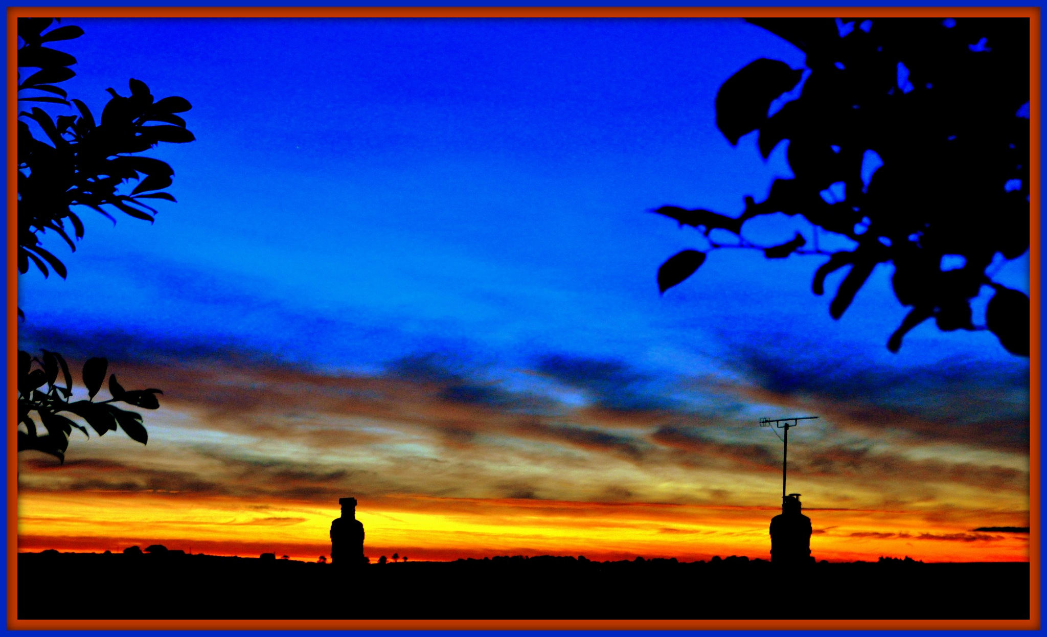 Chimneys watch the sun rise in West Wales by Colin Spence
