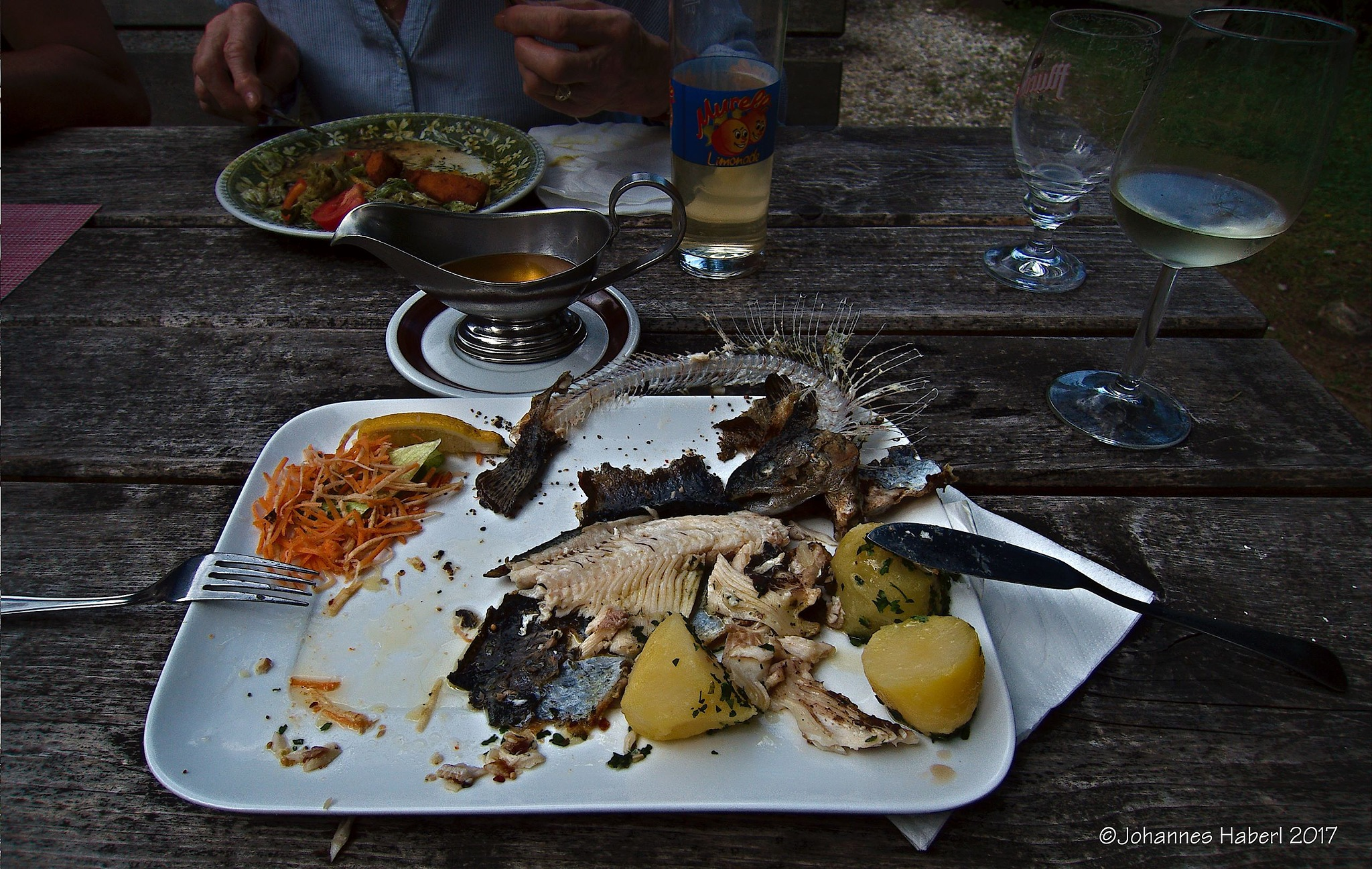 trout on the table / with melted butter and parsley potatoes  by Johannes Haberl