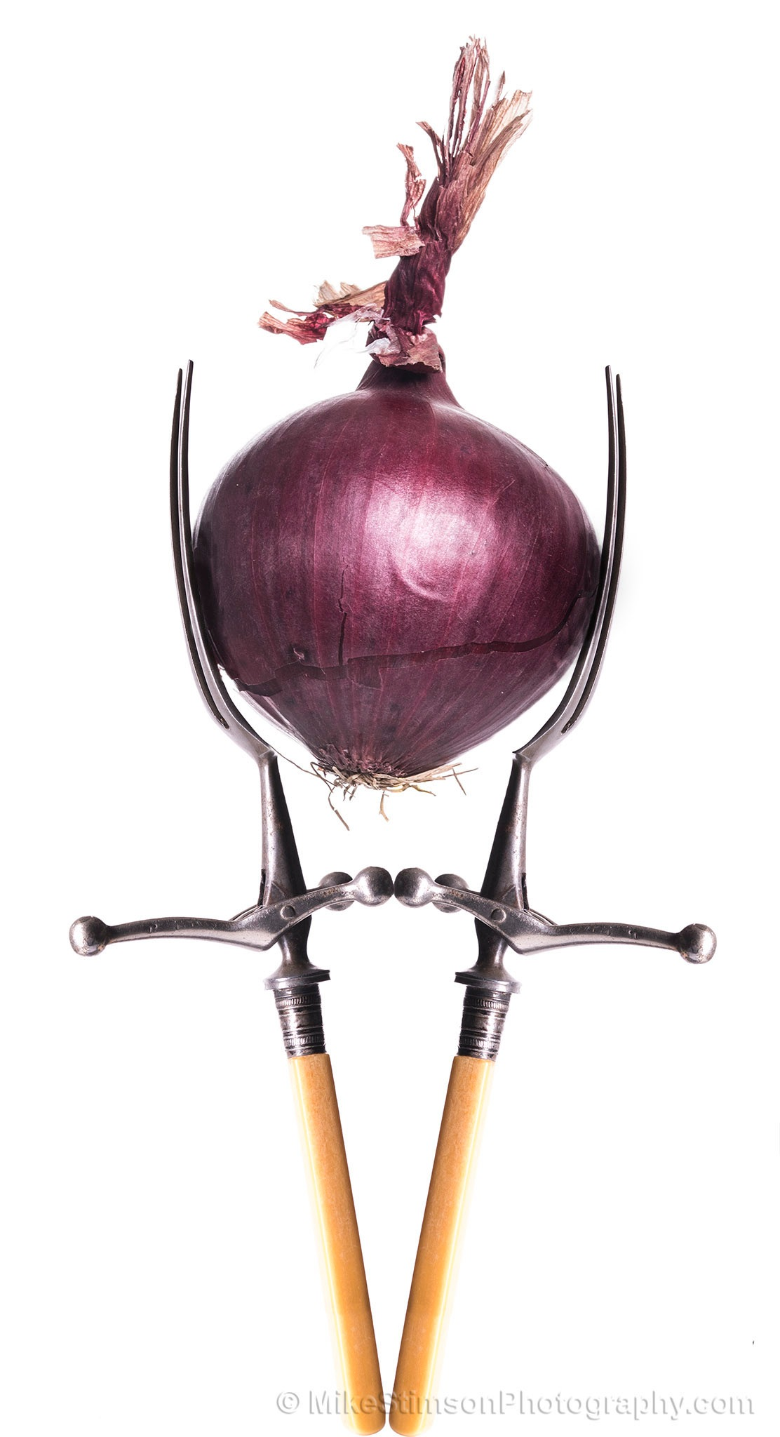 Red Onion, gripped between two antique carving forks by Mike Stimson