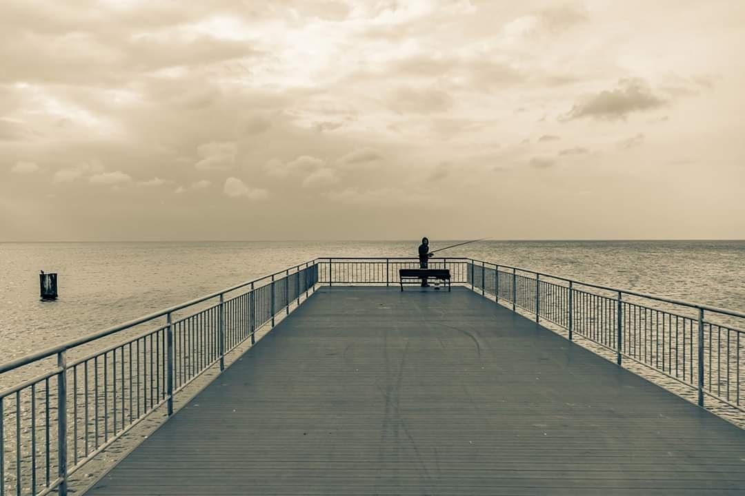 fisherman on pier by Yılmaz Savaş Kandağ
