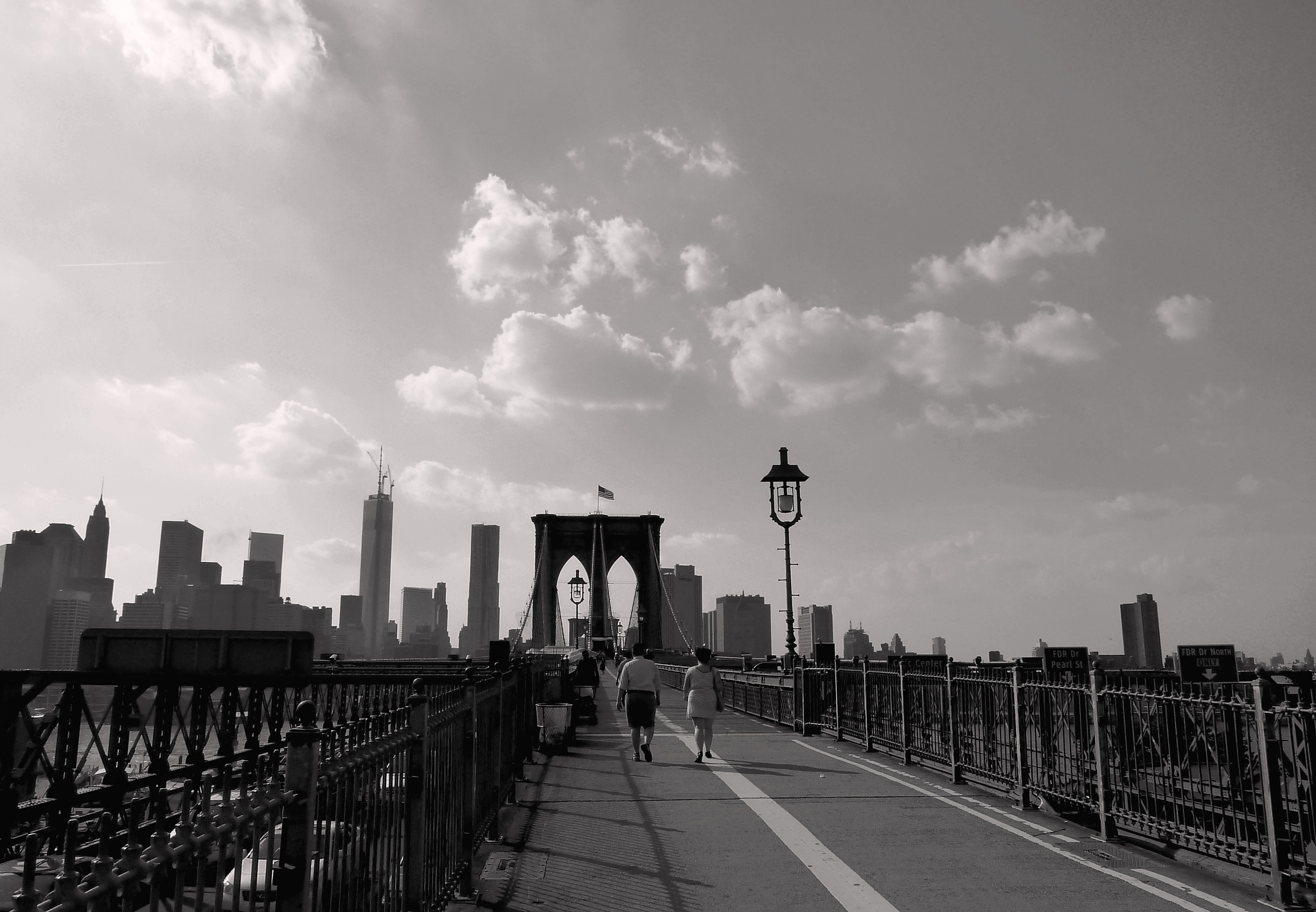 Crossing to Manhattan.  On the Brooklyn Bridge, NYC. by Anton Agalbato