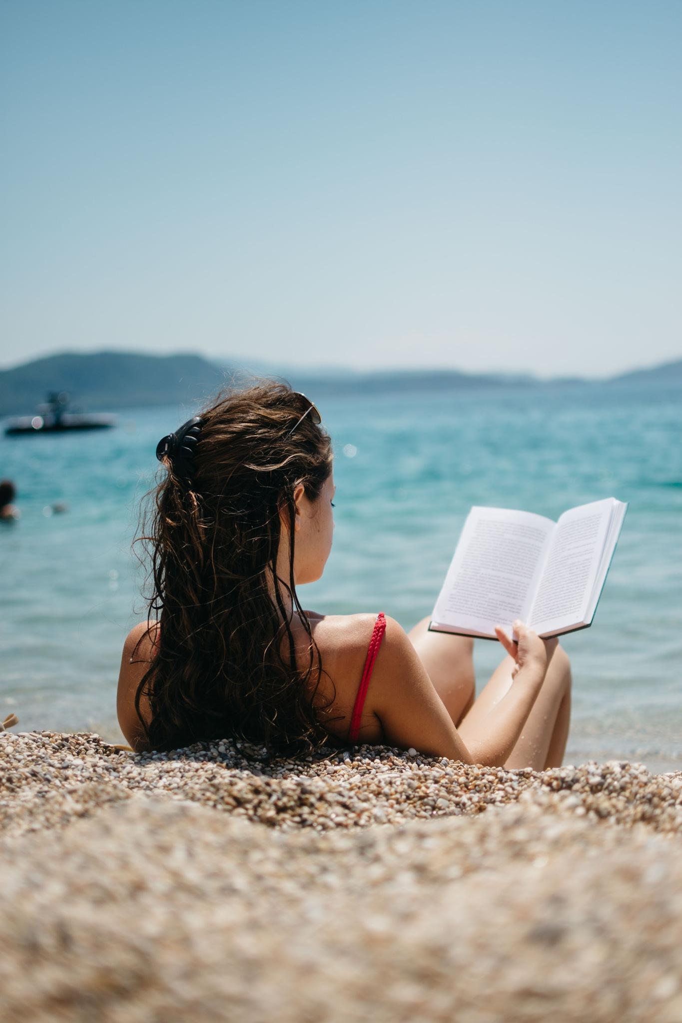 Girl read a book on a beach by Vuk Šarić