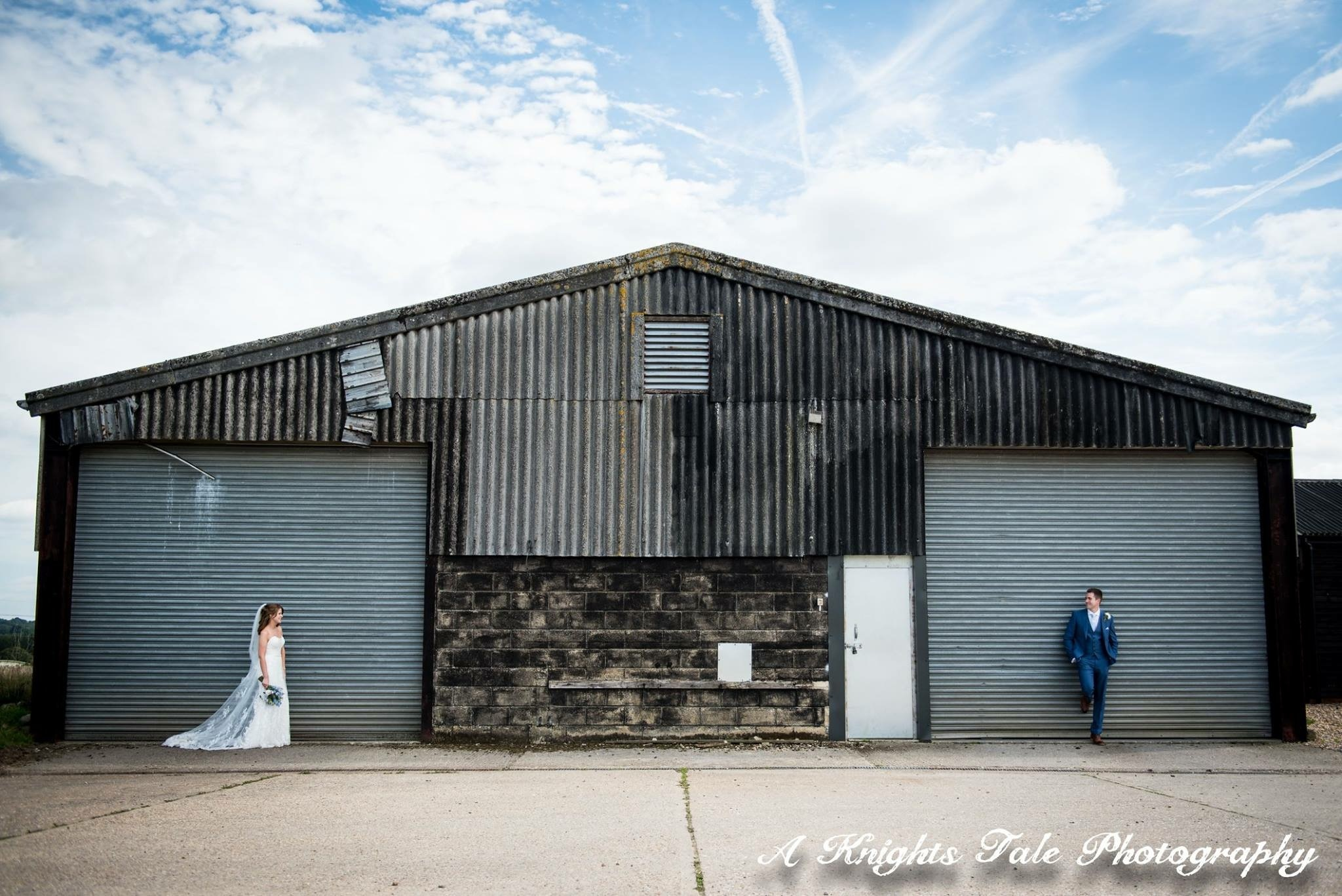 Bride and groom outside barn by Adam Knight