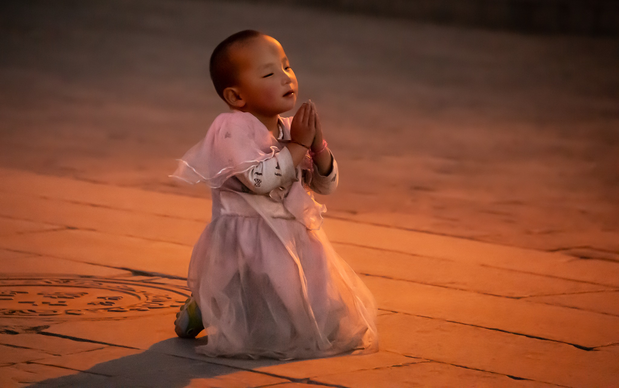 little girl praying in lhasa by Ron Conigliaro