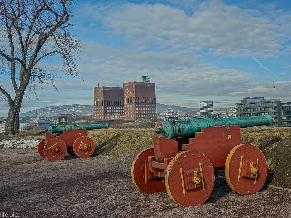 Ancient cannons over the castle towers overlooking the city hall of Oslo by LifePics