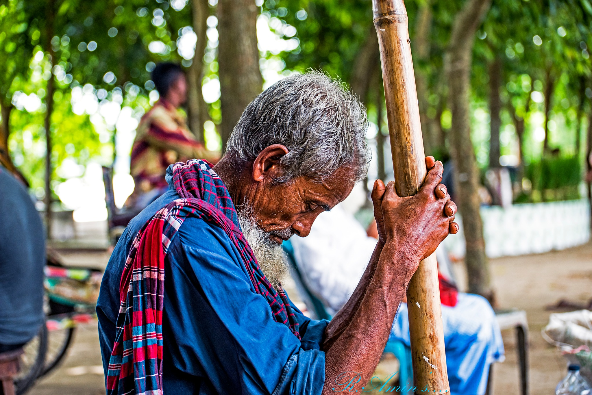 A Tired old Men sleeps on the street and hold bamboo with two hands.... by Md. Ruhul Amin