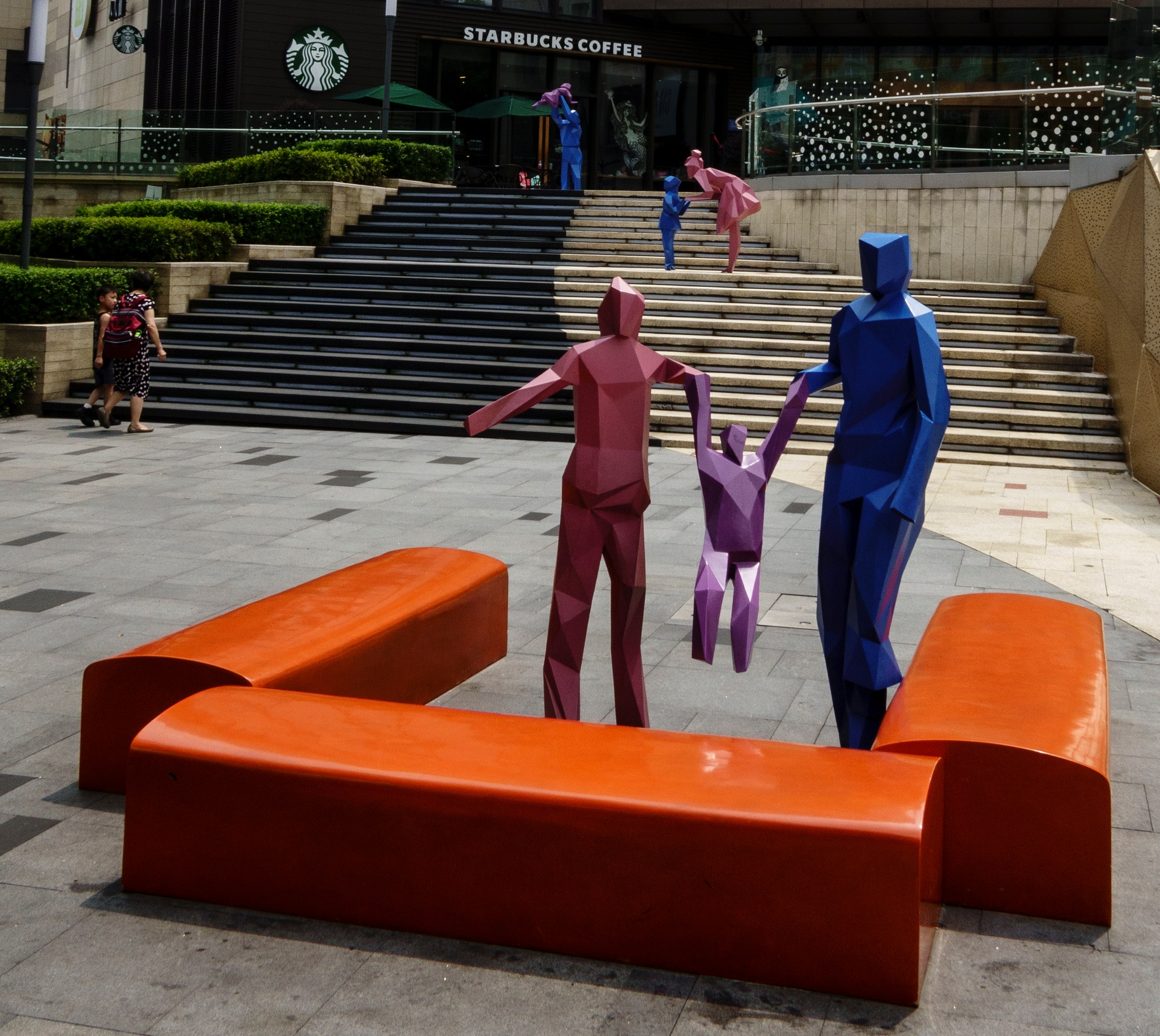 Humans and sculptures outside a shopping center in Chongqing by JonArneFoss