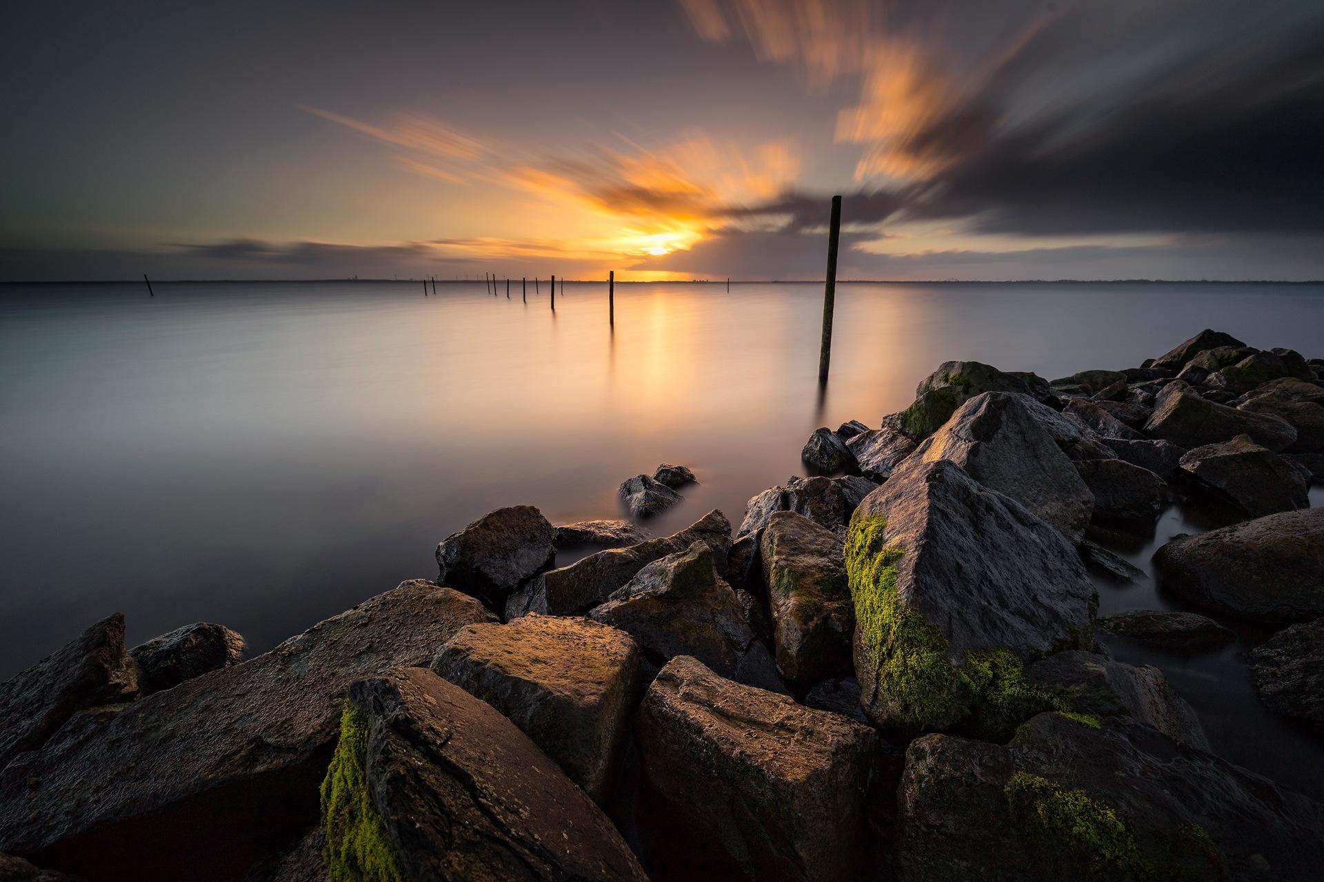 Photo in Landscape #lake #rocks #sunrise #amsterdam #poles