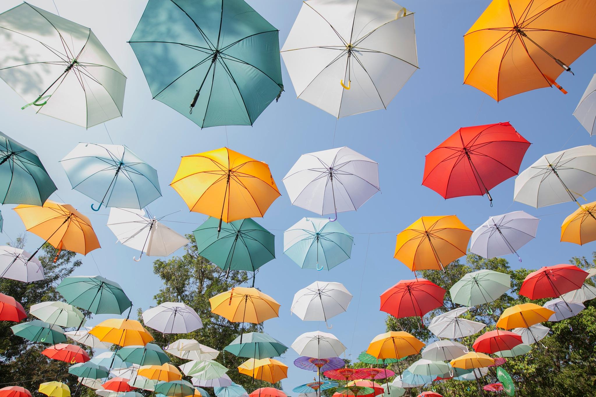 Hanging colored umbrellas by Helga Kuiper
