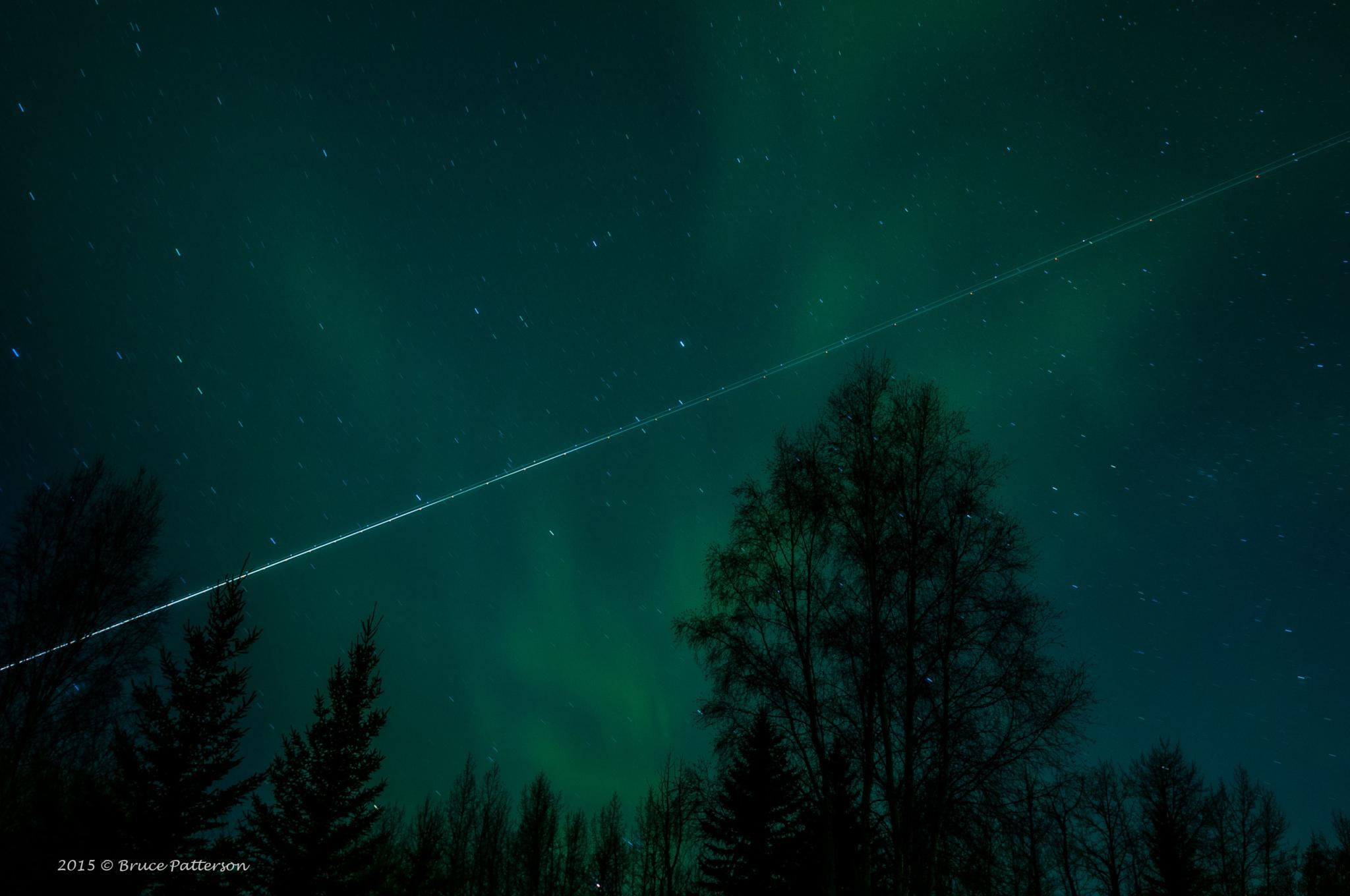 Jet Trail Over the Northern Lights. by Bruce Patterson