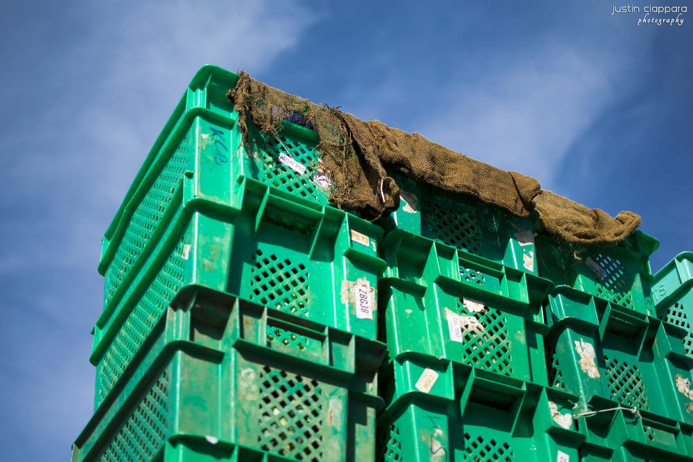 Stack of Crates filled with different types of vegetables ready to be sold by Justin Ciappara