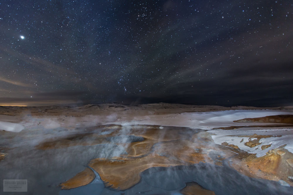 Fire & Ice - A geothermal pool in a frozen landscape on a starry night. by Sigurdur William Brynjarsson