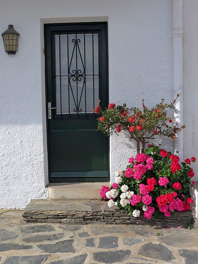 Photo in Architecture #flowers #entrance #door #stones #lamp #step #white #red #geraniums
