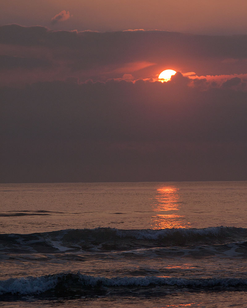 The rising sun peeking its head out from between the clouds by Brian Hammersley