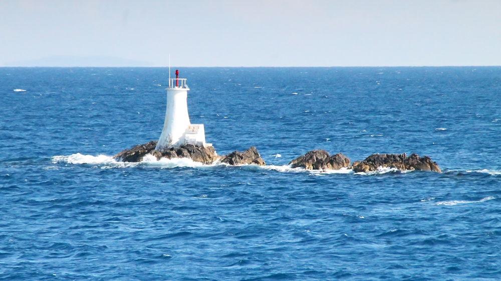 Lighthouse on rocks by oliversvob