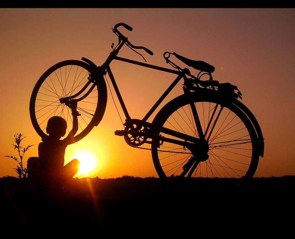 Silhouette of a child with a cycle by Kush Sahani