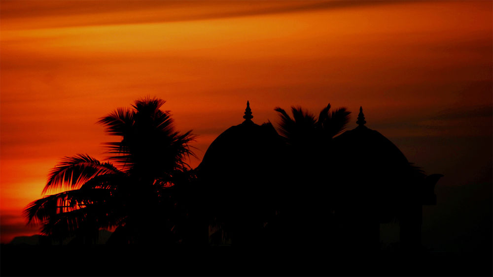 The sky turning red as the sun sets behind a small temple by Raj Marlecha