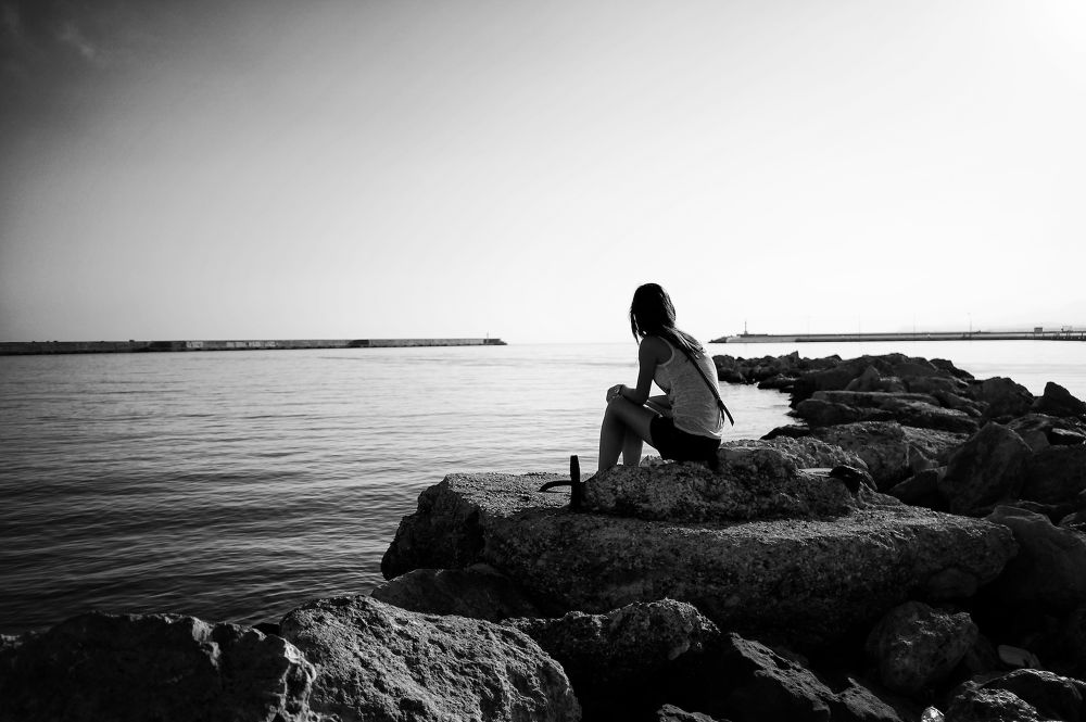 Photo in Street Photography #mono #monochrome #b&w #b&w photography #morning #day shot #day #sea #sky #girl #woman #rocks #rethymno #crete #greece #20mm #sel20f28 #sony nex #nex-6 #water #harbour #sitting #looking #thinking #street photography #candid photography #candid