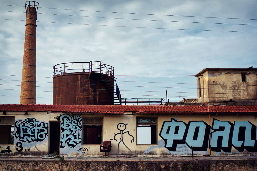 Photo in Street Photography #colour photography #color #street photography #sky #clouds #graffiti #factory #chimney #chair #sony nex #nex-6 #35mm #sel35f18 #rethymno #crete #greece