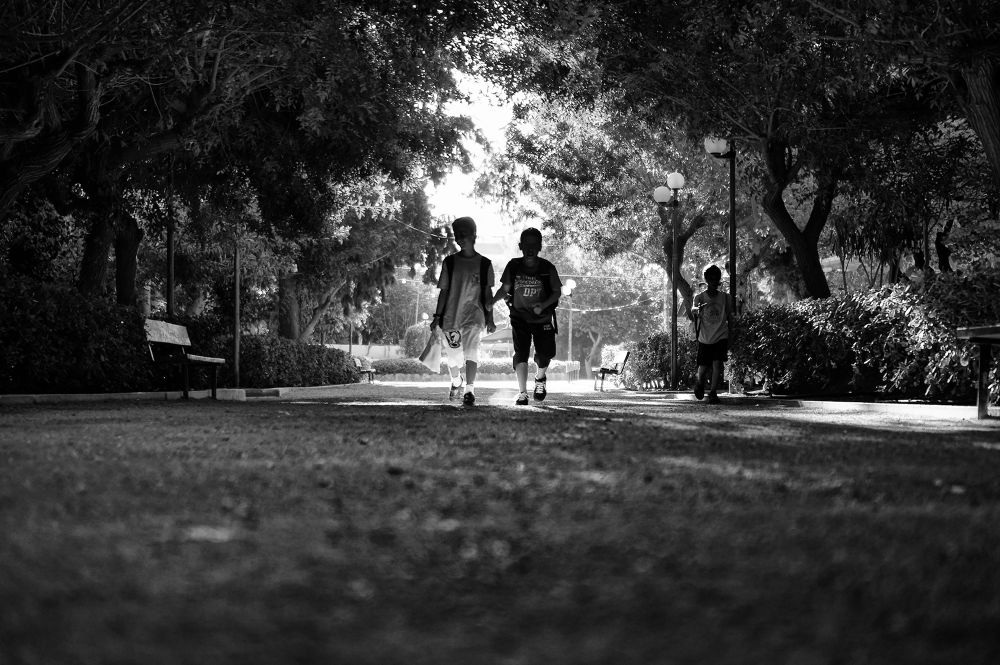 Photo in Street Photography #mono #monochrome #b&w #b&w photography #kids #children #walking #street photography #street hunters #candid photography #trees #light #shadows #rethymno #crete #greece #ground level #rat's eye view #35mm #sel35f18 #sony nex #nex-6