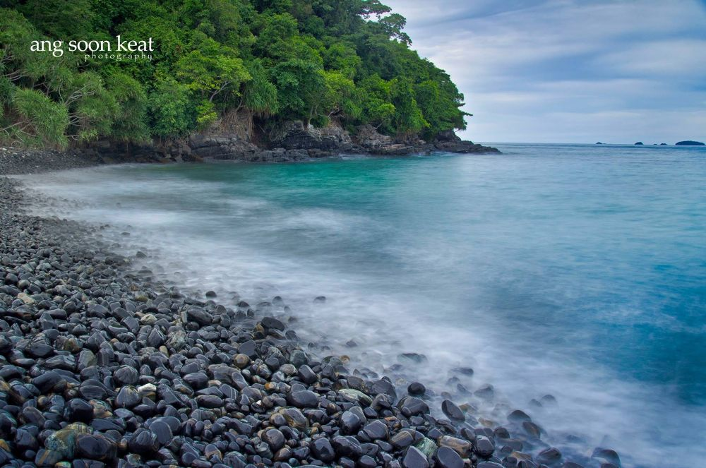 An island with black rock nearby Koh Lipe island, Thailand by soonkeatang23