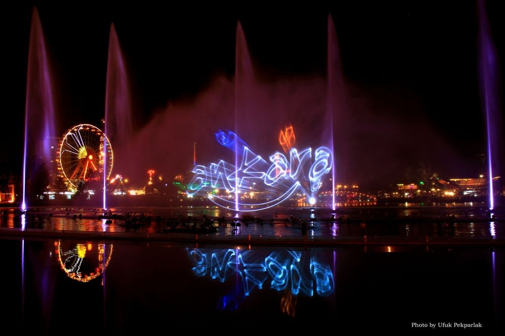 Photo in Urban #water and light #youth park #sprinkler #funfair #ferris wheel #colors #night #reflection #long exposure
