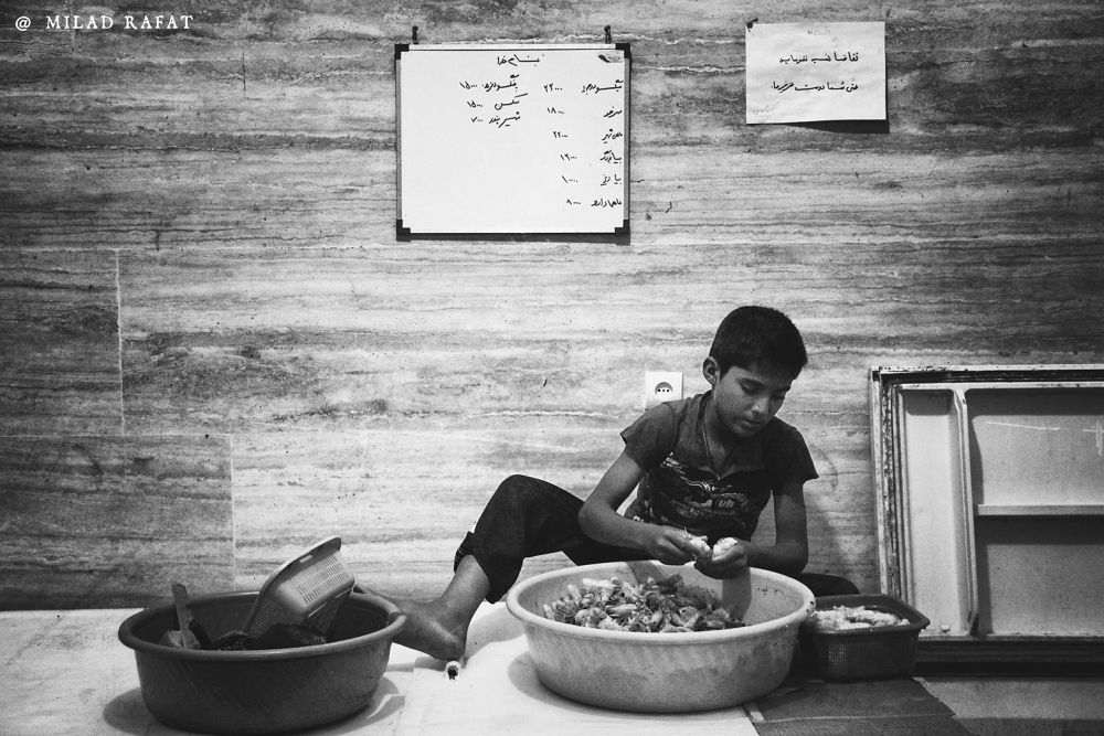 A Boy remove skin of Shrimps by Milad Rafat