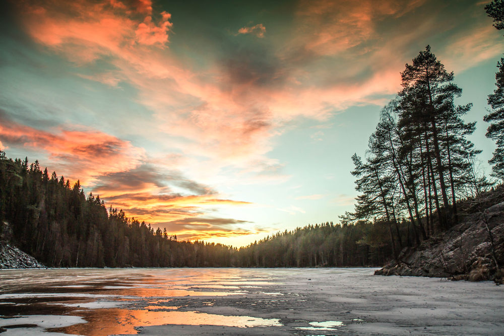 Sun set over frozen lake by henrikbekken