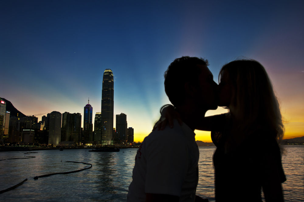 Photo in Cityscape #hongkong #city #kiss #evening #sunset #building #lights #architecture #love #people #traveling #man #woman #couple #sea #reflection