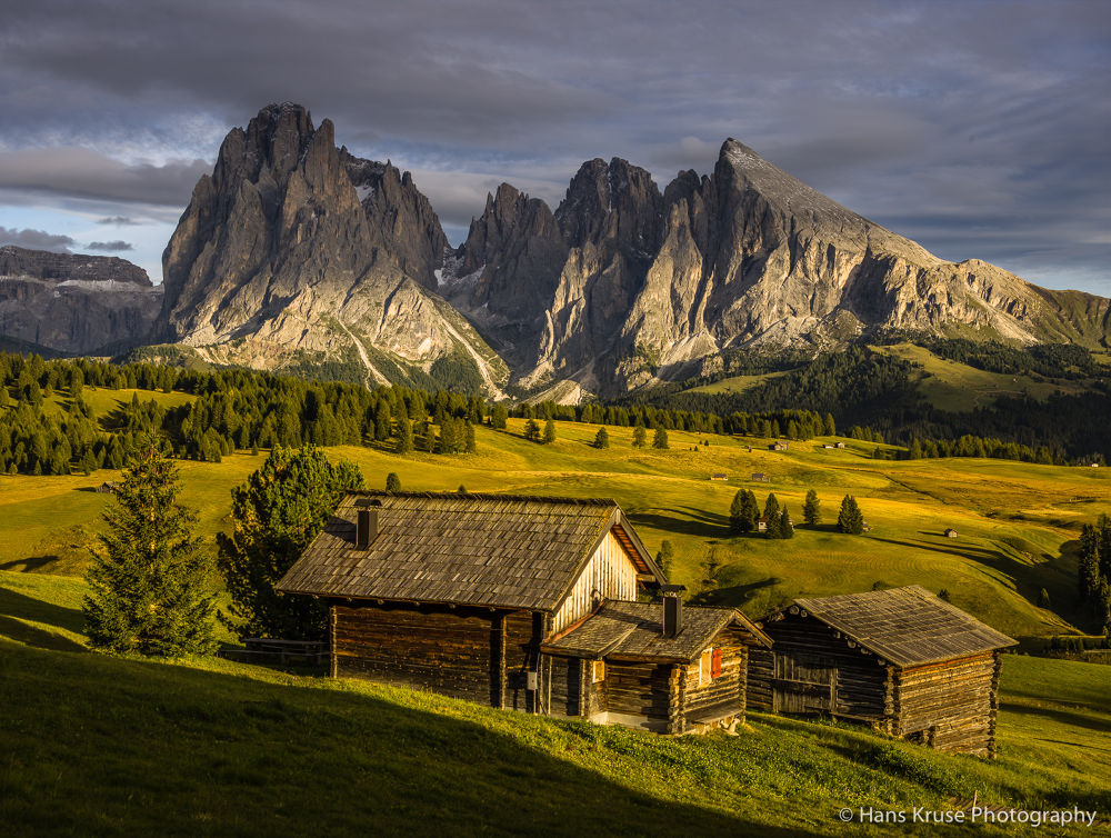 Houses on Alpe di Siusi in late afternoon light by Hans Kruse