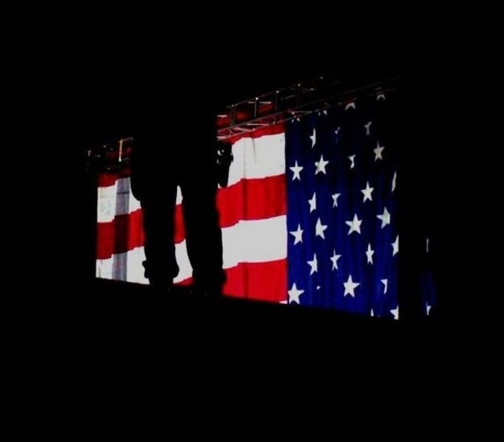 Behind the Flag (Taken at Obama's speech the night before Election Day 2008) by FreeBirdStudios