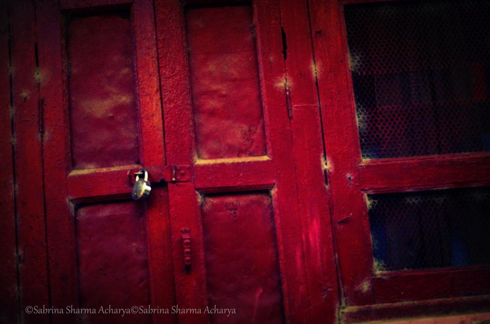 A torn window and an ancient locked door. by Sabrina Sharma Acharya
