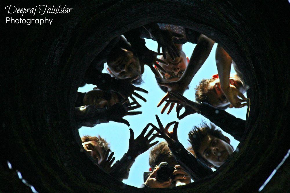 Friends, reflection inside deep well, directly above  by Deepraj Talukdar