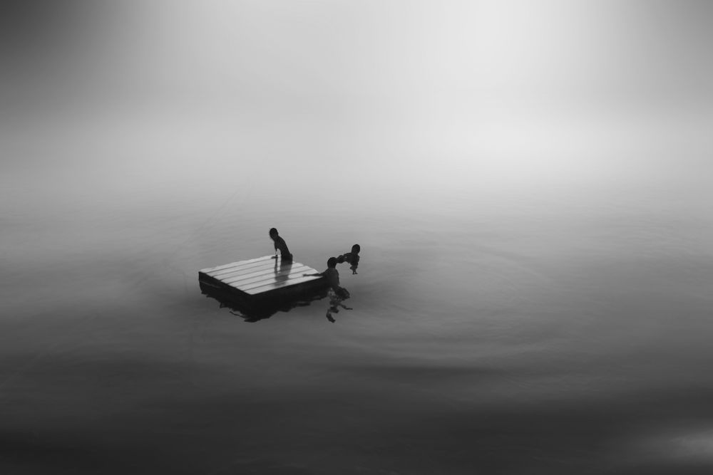 3 kids with raft BW by Robby Montolalu