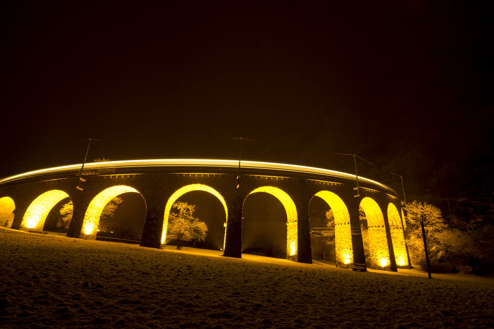 Train over Brusio viaduct in a snowing night by Ivan Piani