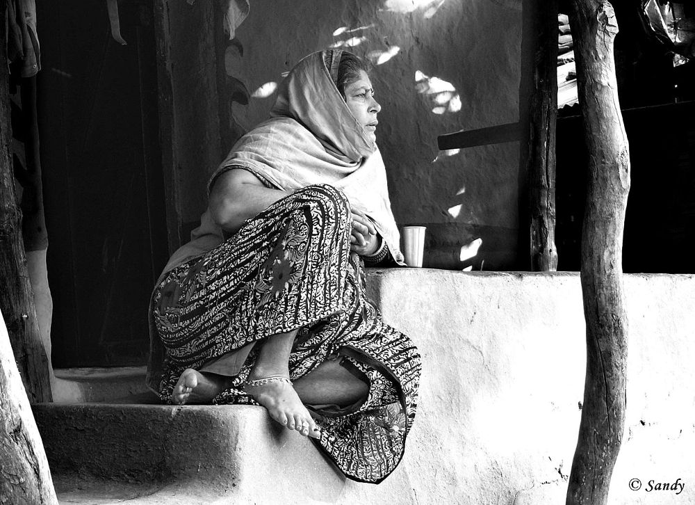 Indian village woman enjoying morning sun and a glass of tea. by drsandy