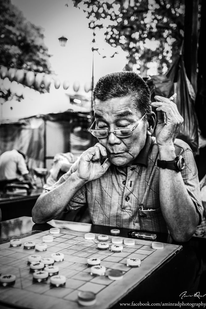 An old man  playing chess at Chinatown  by AminRad