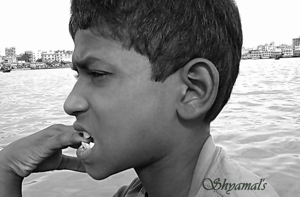 A MINOR BOY ON BOAT IN RIVER THOUGHTFUL by ShyamalKBanik