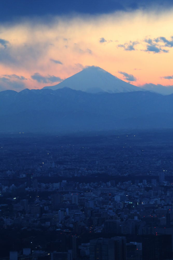 Mt. Fuji against cityscape sunset by Mona Ohya