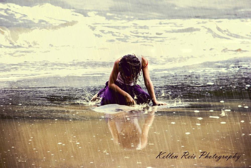 A girl playing close to the beach and basking in the rain by Kellen Reis