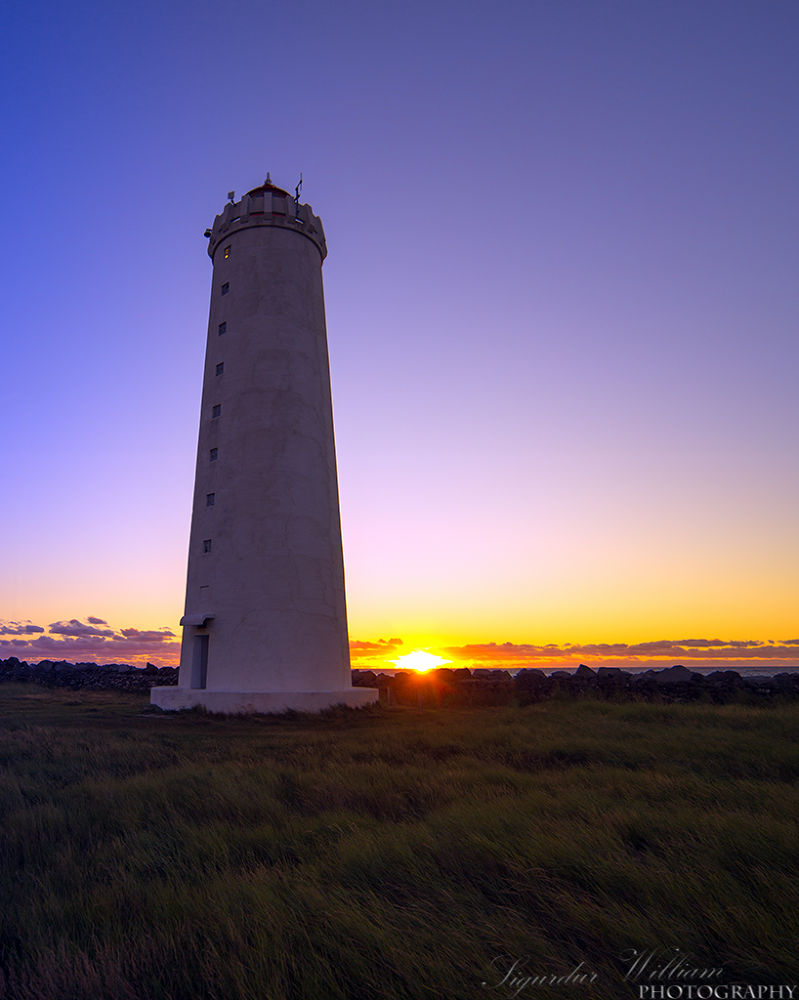 Sunset by a lighthouse by Sigurdur William Brynjarsson